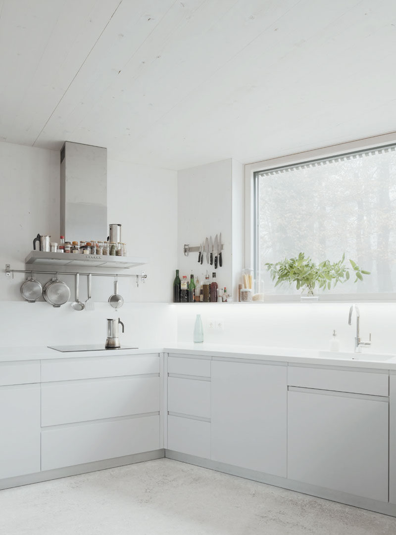 In this modern kitchen, white cabinets and hidden lighting have been used to keep the bright and airy.
