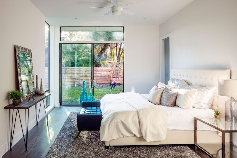 This master bedroom suite has access to the backyard, while wooden floors and a light brown rug have been paired with a cream colored bed and light walls.
