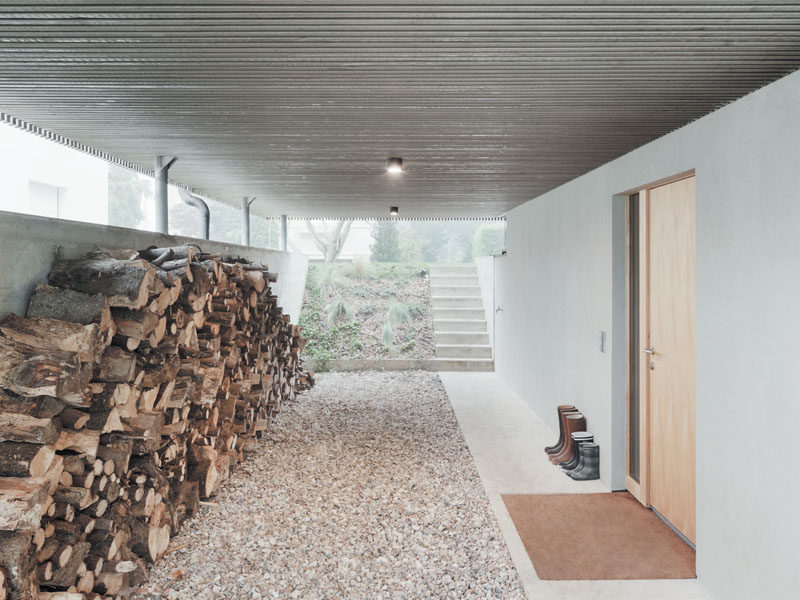 The carport underneath this modern provides access to the home and allows for firewood to be stored. Steps at the rear of the carport lead to the backyard.