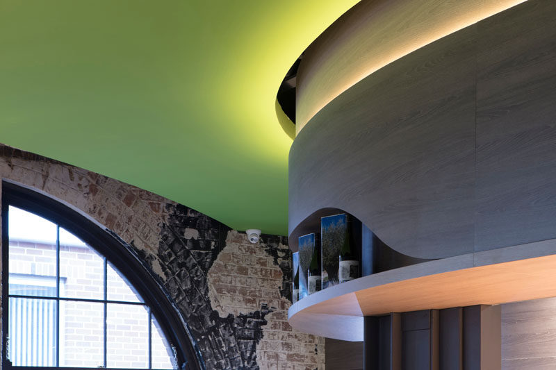 Hidden LED lighting features at the top of these curved wooden panels to highlight the edges of the olive green ceiling.