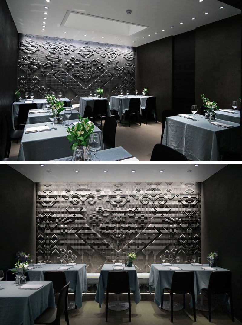 Wall Decor Ideas - In the dining area of this modern restaurant is a stone tapestry that covers the entire wall with pattern inspired by the lapwing bird.