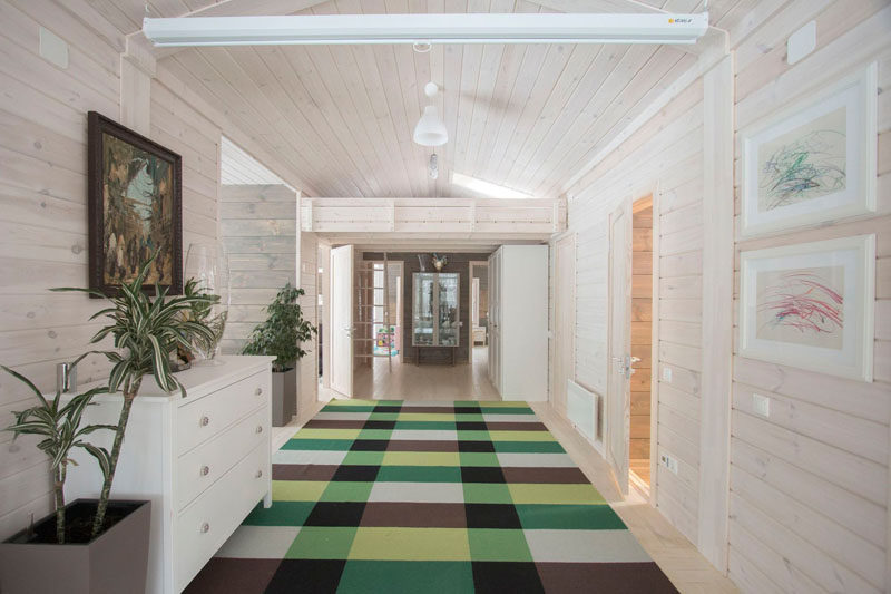 This light wood hallway in this rustic modern house is made from solid pine that's then painted white. A colorful checkered rug leads you to the bedrooms at the end of the hall.