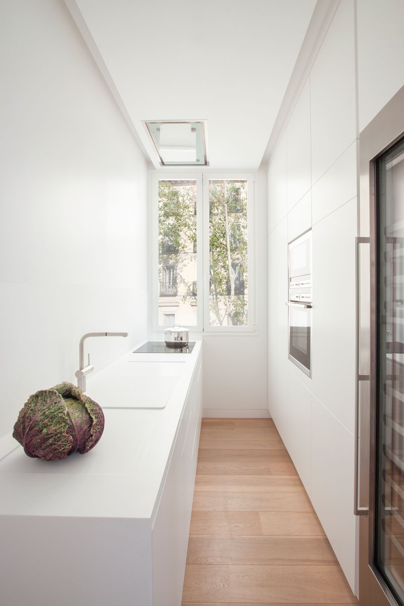 This galley kitchen has minimalist white cabinets on one side for storage, while the opposite side of the modern kitchen has the countertop, sink and cooktop. As the kitchen is white, the light from the tall windows at the end of the kitchen reflects throughout the space, making it bright and airy.