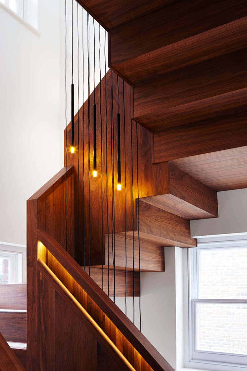 Small pendant lights have been hung down the middle of this staircase with built-in handrails to add more soft lighting and compliment the lights inside the railings.