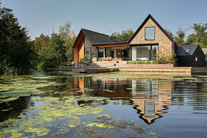 This new modern house covered in wood shingles has pitched roofs, a separate boat shed, sits beside a secluded lagoon and can also be rented out for vacation rentals.