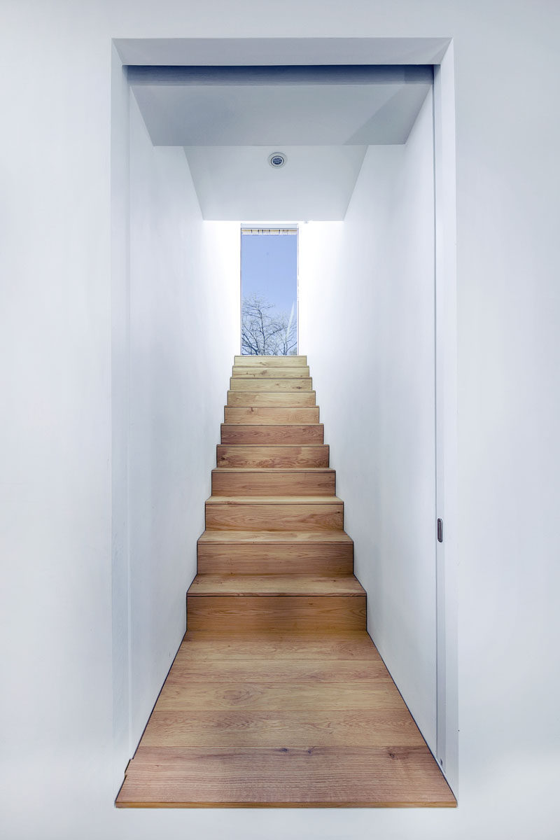 White walls and wooden stairs lead you up to the upper level of this modern holiday home.