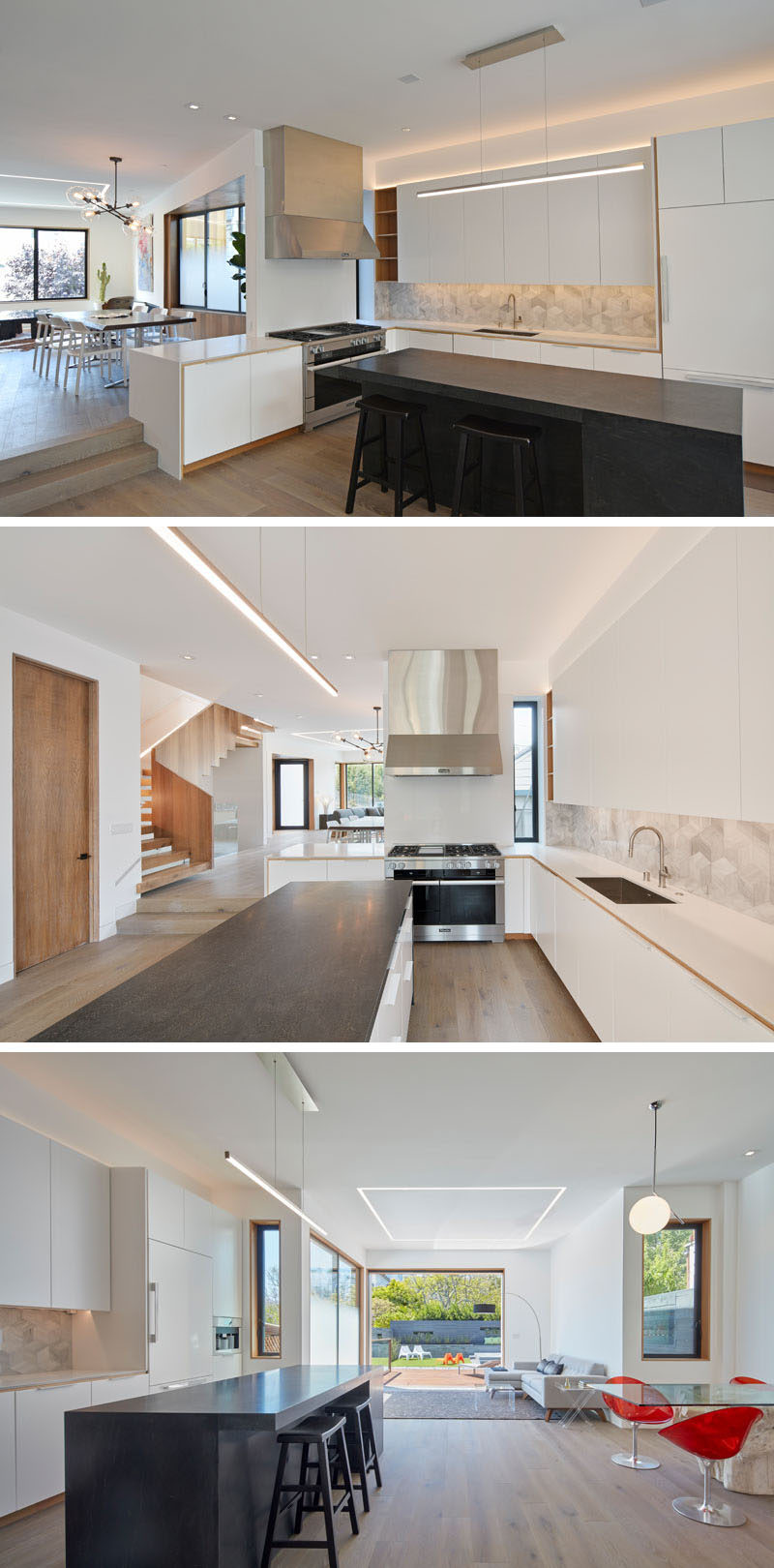 Stepping down from the dining room in this modern house is the kitchen. A large black central island with seating contrasts the white cabinets and countertops, and stainless steel appliances. Off to the side of the kitchen is a small dining nook with red chairs and a glass table.