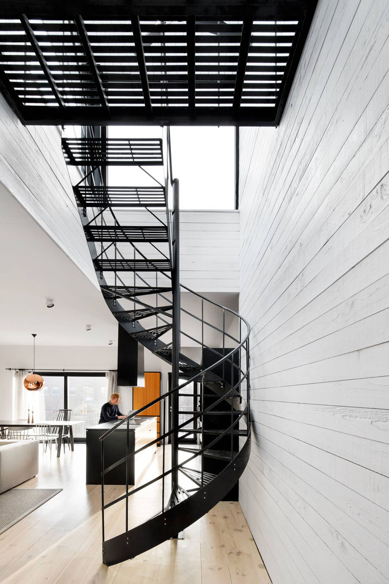 A simple matte black metal spiral staircase with grated steps connects the two main floors of this modern house and lets light easily pass through to keep the space feeling bright and airy. #SpiralStairs #SpiralStaircase #ModernSpiralStairs