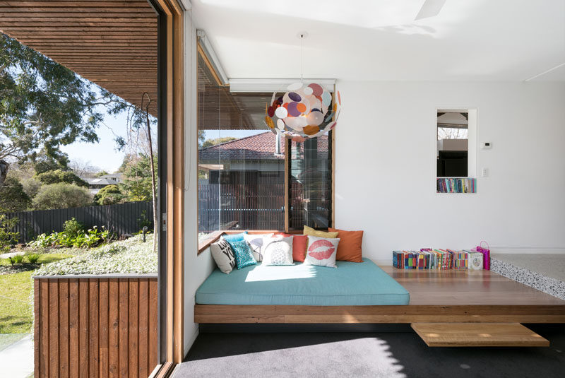 This modern house features a built-in daybed with a thick mattress on top, and it sits up against a wrap-around corner window to create a cozy reading spot lit up by both a colorful pendant light and the natural light coming through the windows.