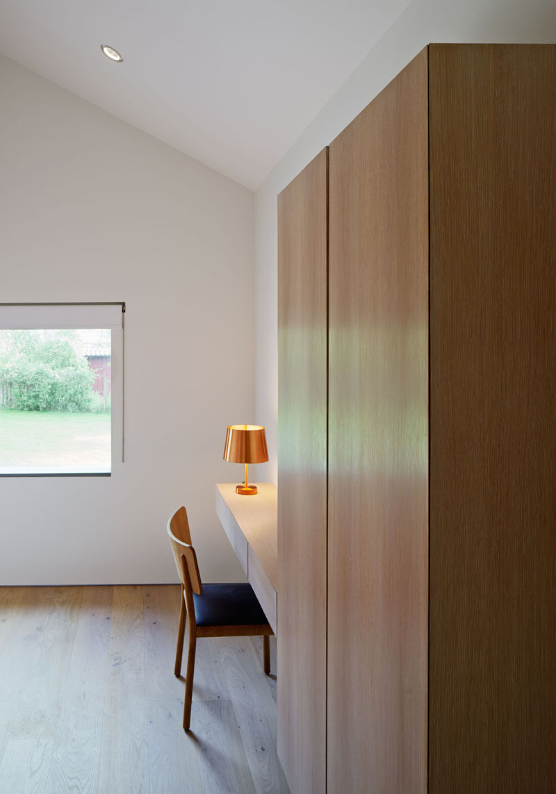 In this modern bedroom, wood cabinets provide storage, and a floating wood desk gives someone a quiet work area.