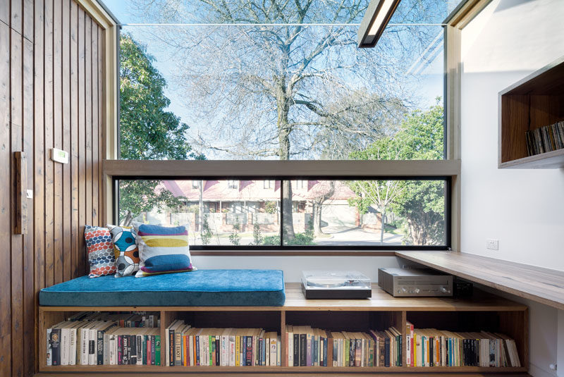 At the very front of this modern house, a built-in reading nook sits beneath a glass ceiling and looks out onto the street. A number of shelving units, including one built into the bench, hold books and music to create the perfect spot to relax and unwind in.