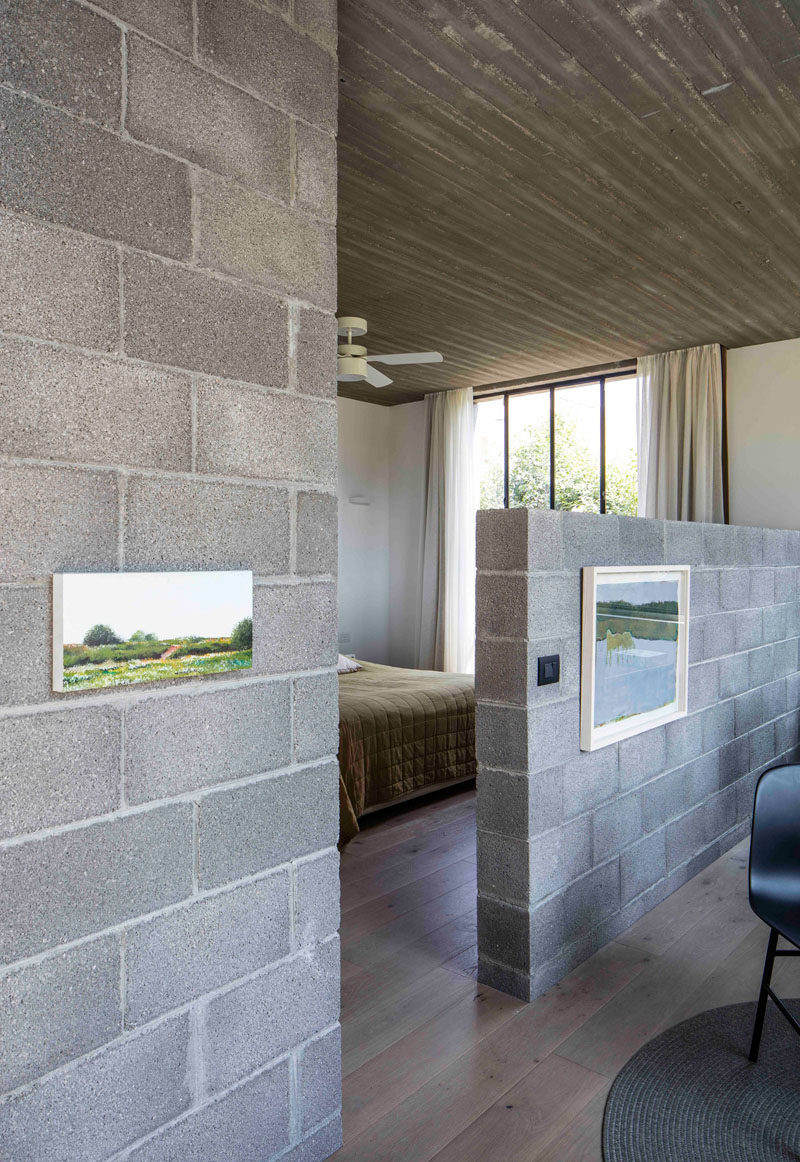 In this master bedroom there's a small sitting room separated from the bed by a pony wall made from concrete blocks.