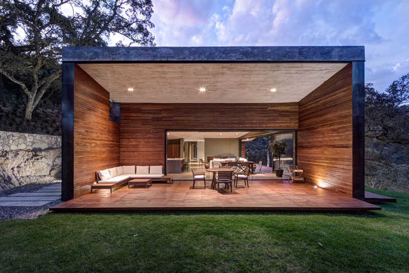 Off to the side of the main living area in this modern house is a large covered outdoor entertaining space. The wood walls surround an additional living and dining area, and protect the area from the elements.