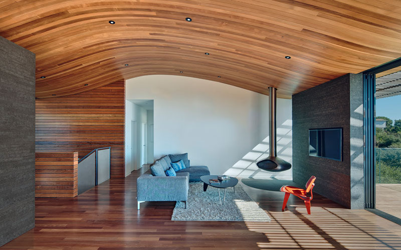 The wood ceiling in this modern living room with a hanging fireplace, mimics the shape of the hill the home sits on.