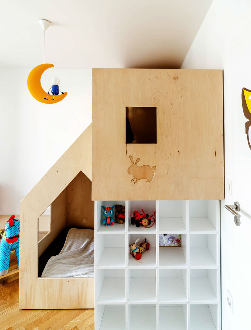 This custom modern plywood bunk bed design in a small kids bedroom houses two beds, a small bookshelf and features multiple wooden cutouts to create windows that allow light into the sleeping space and allows the little kids to look out from the comfort of their beds.