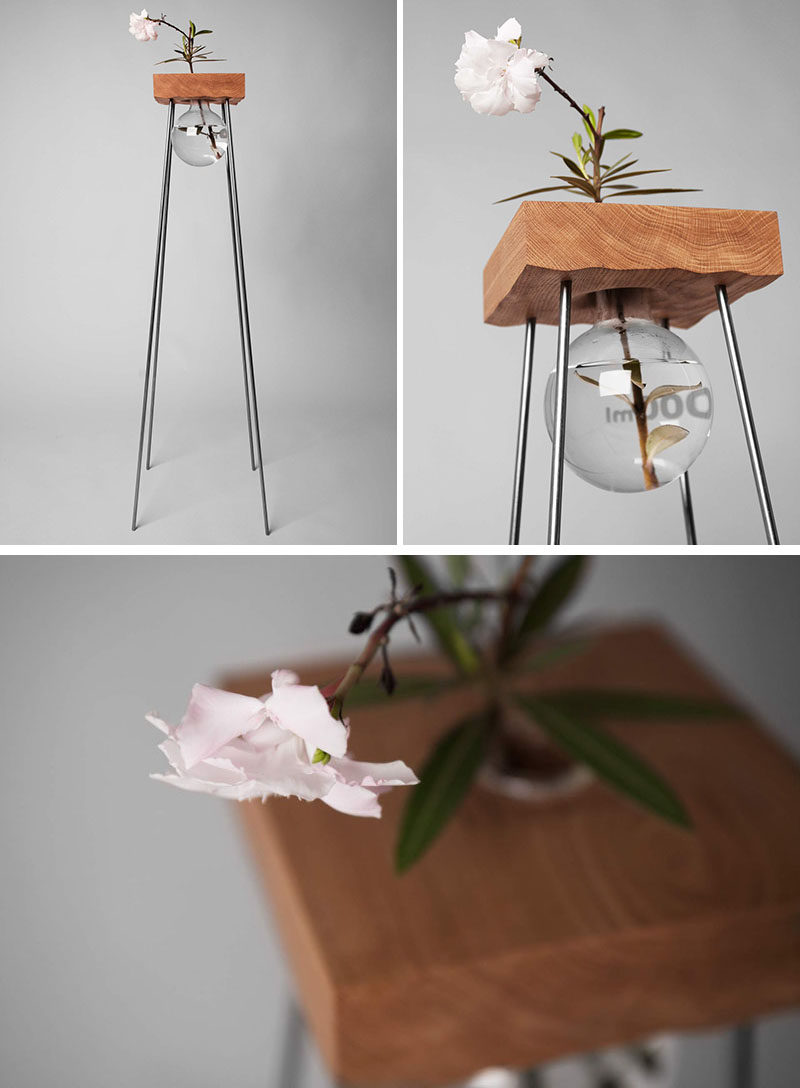 This tall wood and steel table with a simple glass vase has been designed to show off your flower arrangement.