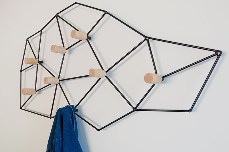 This geometric and modern wall-mounted coat rack could easily pass as wall art, and is made from a black metal frame that attaches to the wall, while wood pegs are positioned at the internal joints, creating a space to hang your jacket, scarf or bag.