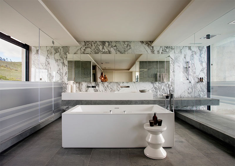 This modern master bathroom has an open-plan layout. In the middle of the bathroom is a freestanding bathtub, while the vanity extends into the large, glass enclosed shower that enjoys views of the city.