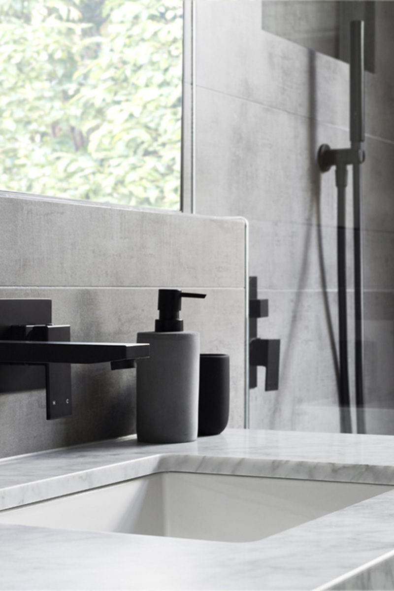 In this modern grey and white bathroom, matte black accents like soap pumps and hardware add a sense of sophistication to the bathroom.