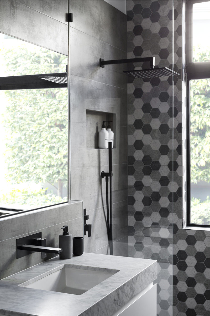 In this modern grey and white bathroom, matte black accents like soap pumps and hardware add a sense of sophistication to the bathroom and shower.