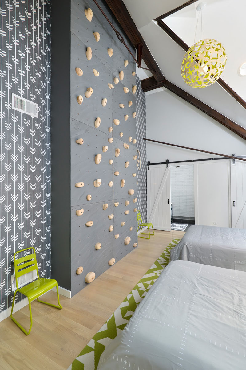 Eight large wood panels covered with rock climbing holds have been installed in this modern bedroom to create a rock climbing wall that can be enjoyed no matter what the weather is doing. #RockClimbingWall #InteriorRockClimbingWalls #InteriorDesign