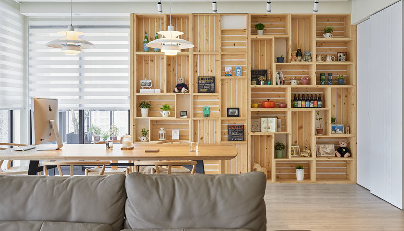 This modern apartment interior features a wall of wood crates that become a bookshelf and add storage to the room