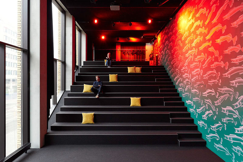 In this modern hotel design, there's an auditorium with rows of tiered seating for talks and lectures to be delivered in an area with lots of natural light and a unique colorful mural along one wall.