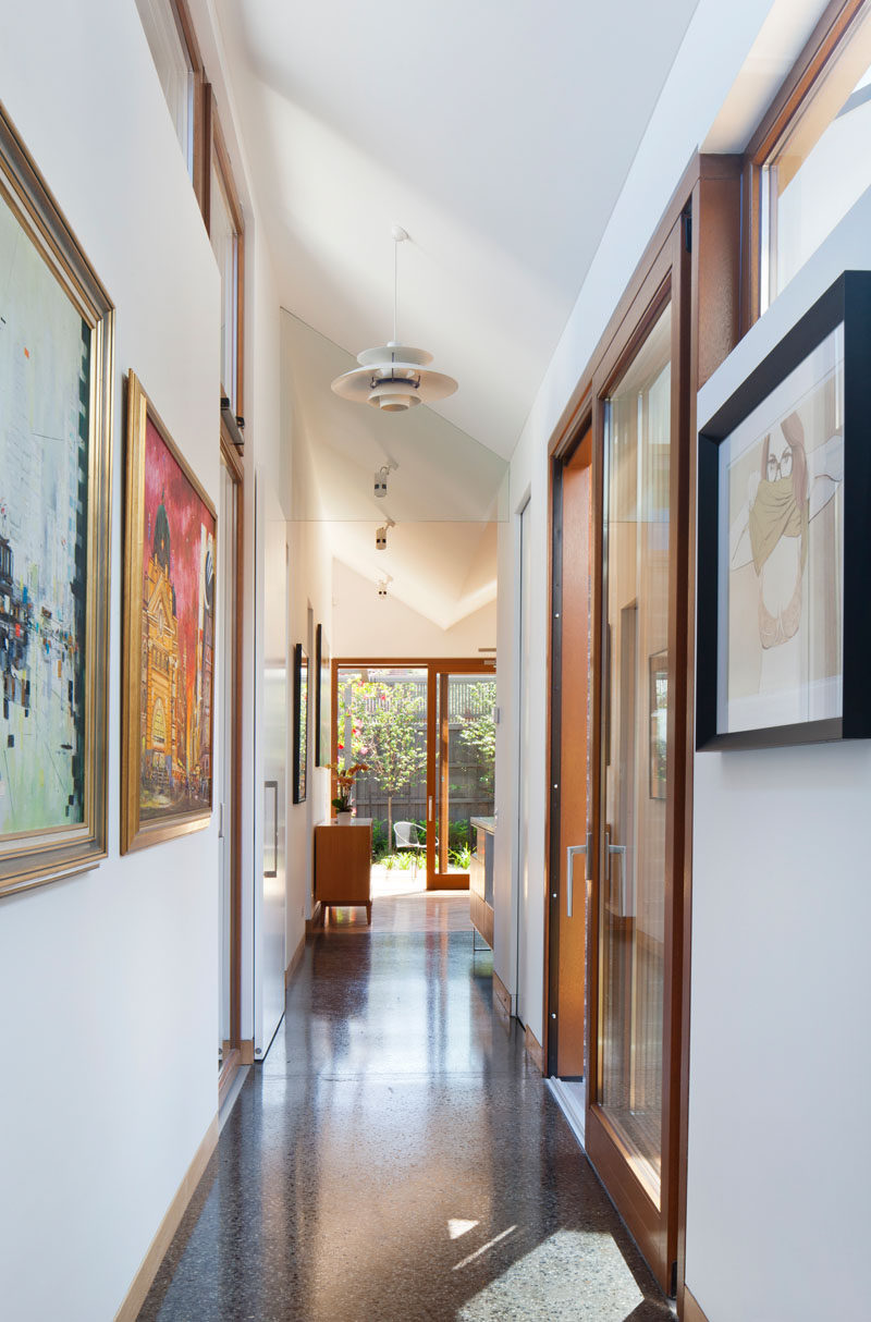 In this modern house, a long hallway lined with art leads to the various rooms or pavilions. White walls and clerestory windows help keep the home feeling airy and naturally bright.