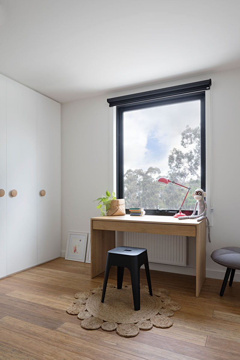 This kids bedroom has a small wood desk positioned in front of the window, perfect for daydreaming and floor-to-ceiling white cabinets have round wood door handles to match the wooden floor and desk.