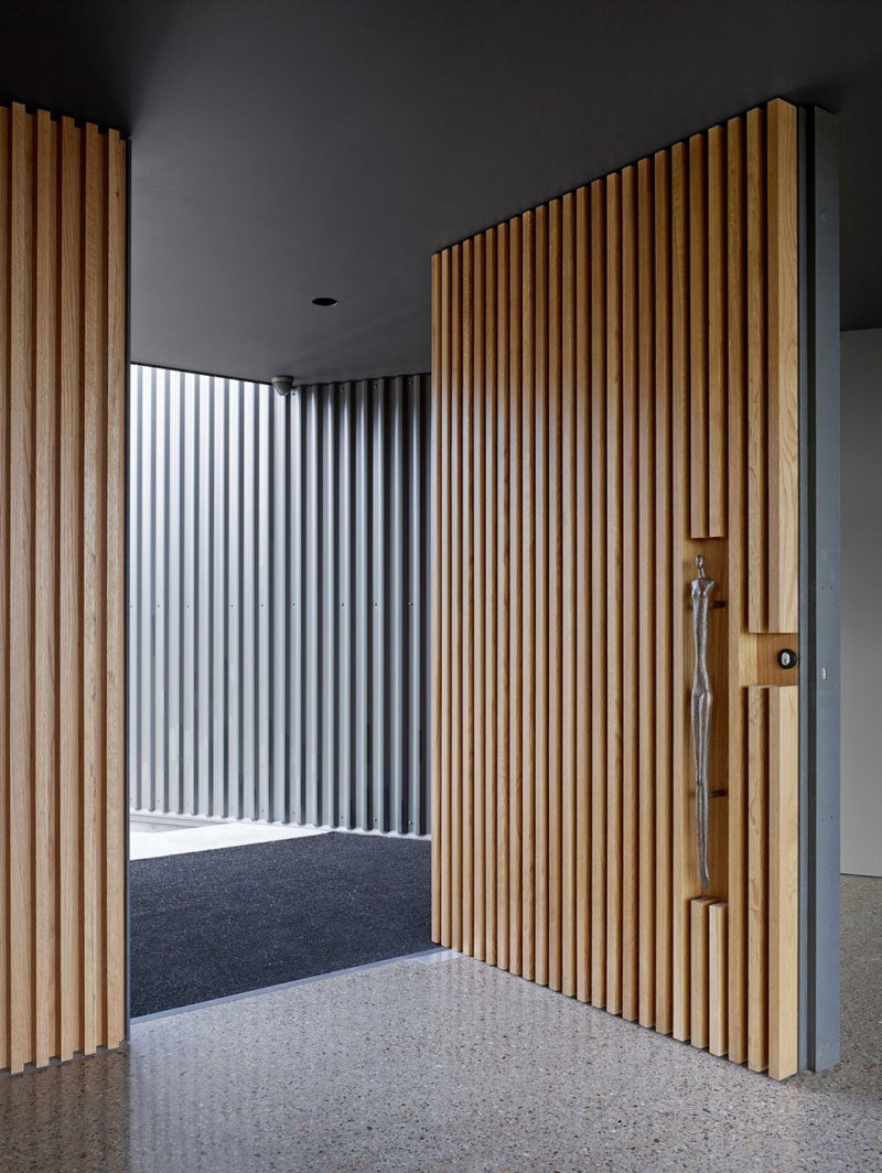 This large pivoting front door covered in light wood slats has a sculptural door handle set into the wood to welcome you into the home. & These 13 Sophisticated Modern Wood Door Designs Add A Warm Welcome ... Pezcame.Com