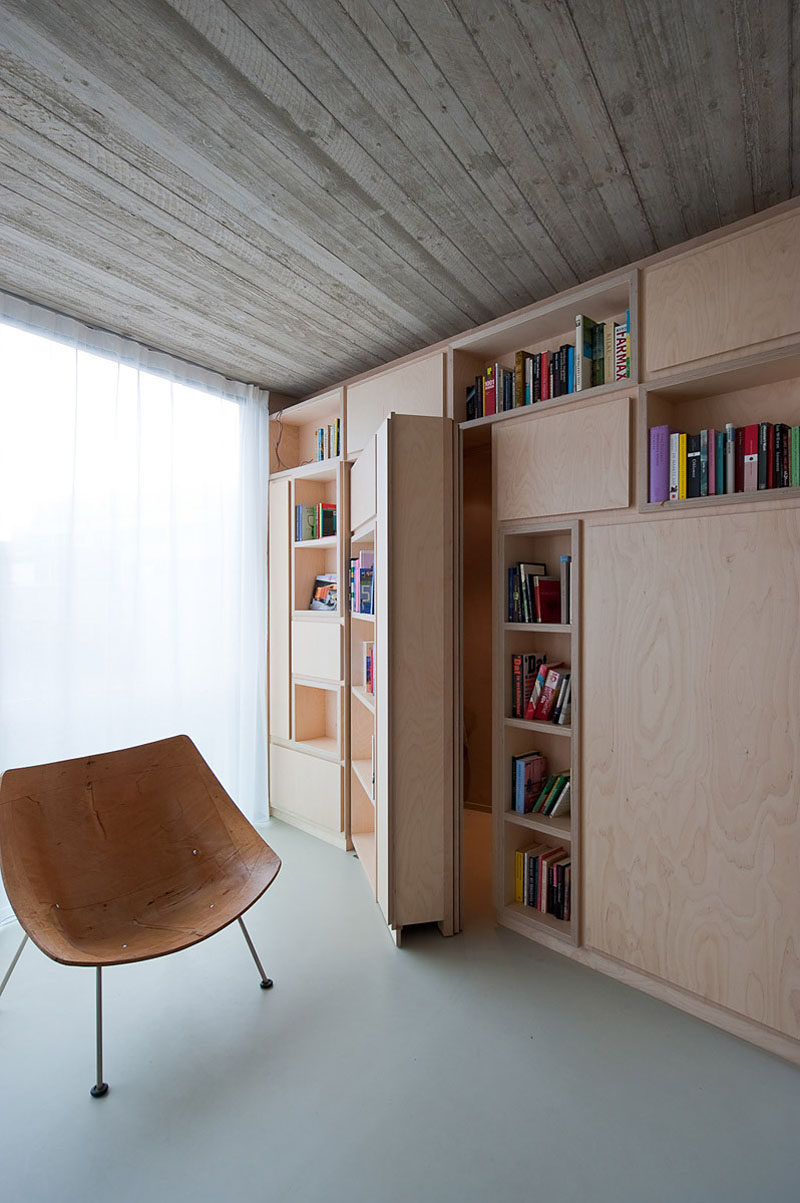 In this small modern house, a private room is hidden behind a wall of built-in bookshelves that can only be accessed by opening the secret door.