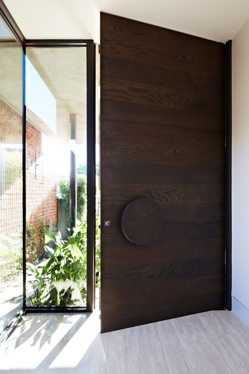 This large dark wood door with the wood grain running horizontally features an oversized circular handle that gives the entry way a modern feel.