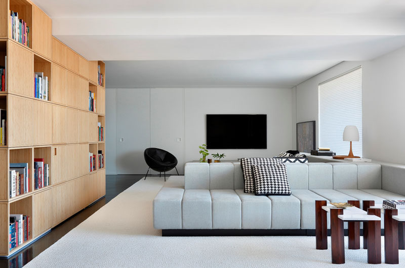 The living area of this modern apartment is divided into two sections by the centrally positioned double-sided couch.