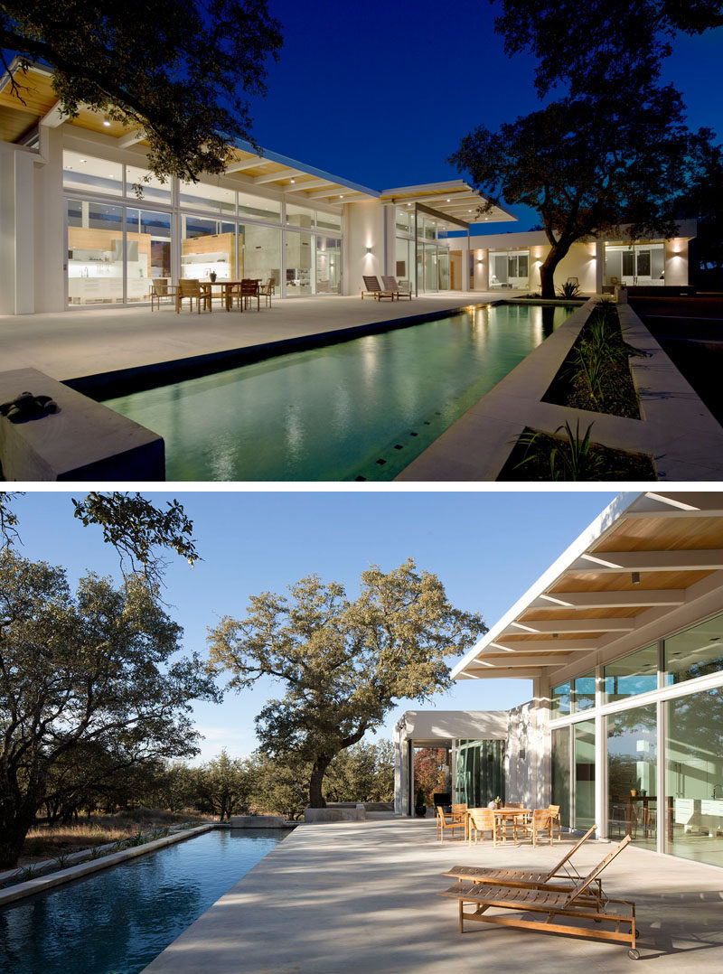 The back of this modern house features oak trees, a long lap pool and a large concrete pool deck that has more than enough space to lounge comfortably, entertain guests, or do both at the same time.