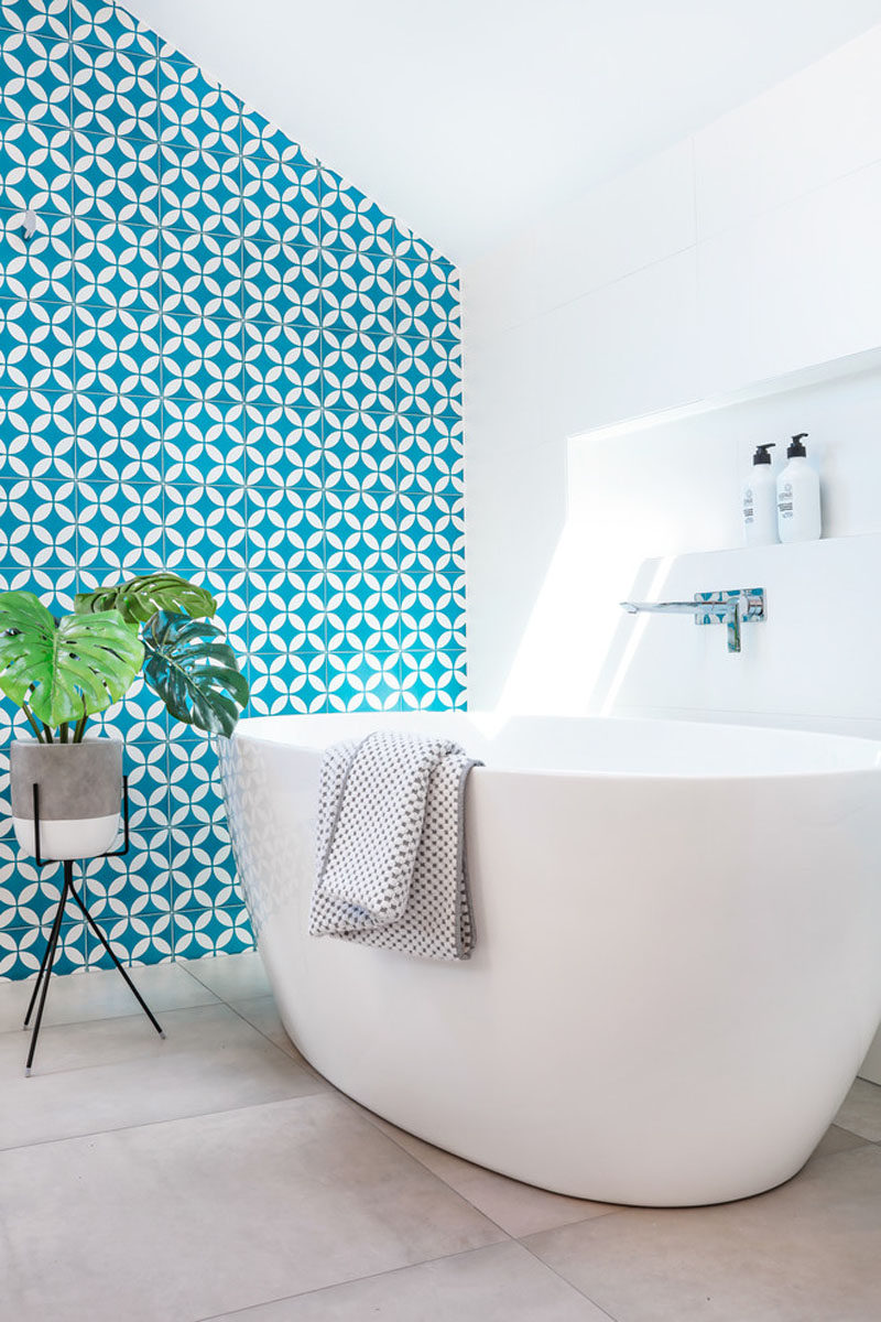 This white and wood bathroom has a bright blue accent wall Bright blue tile