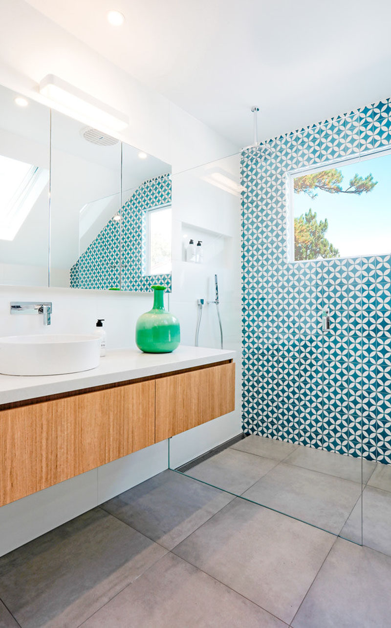 The most attention grabbing aspect of this mostly-white modern bathroom is the bright blue and white patterned tile accent wall that works well with the large grey porcelain floor and the floating wood vanity and built-in closet.