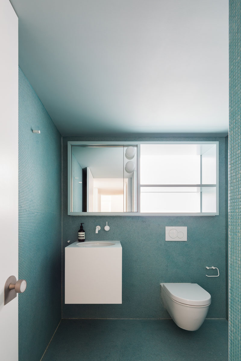 In this modern master bathroom, the tiny square turquoise tiles on both the walls and the floor create a monochrome look that's interrupted by the floating white vanity, the toilet and the large mirror that doubles as a storage cabinet.