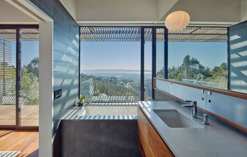 This modern bathroom with a large mirror features a built-in bath perfectly positioned to take advantage of the views.