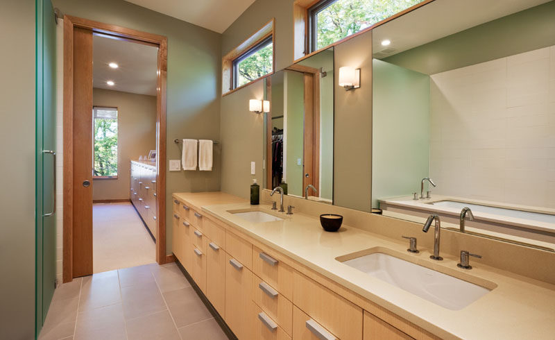 In this modern bathroom, windows along the top of the wall keep the space naturally bright, and a double vanity sink with lots of built in storage lets two people comfortably get ready at the same time.