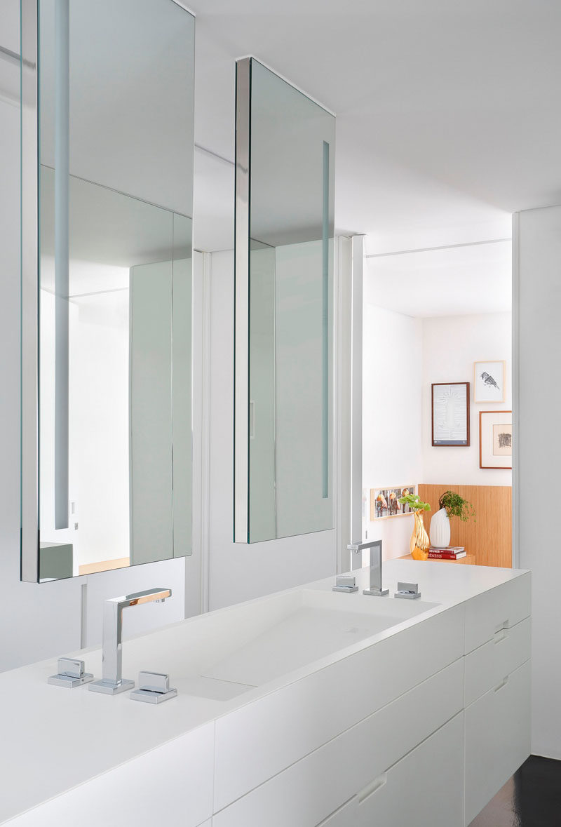 This modern ensuite bathroom that also doubles as a dressing room, features white Corian countertops and double vanity with two hanging mirrors that help brighten the space by reflecting back the all white cabinetry.