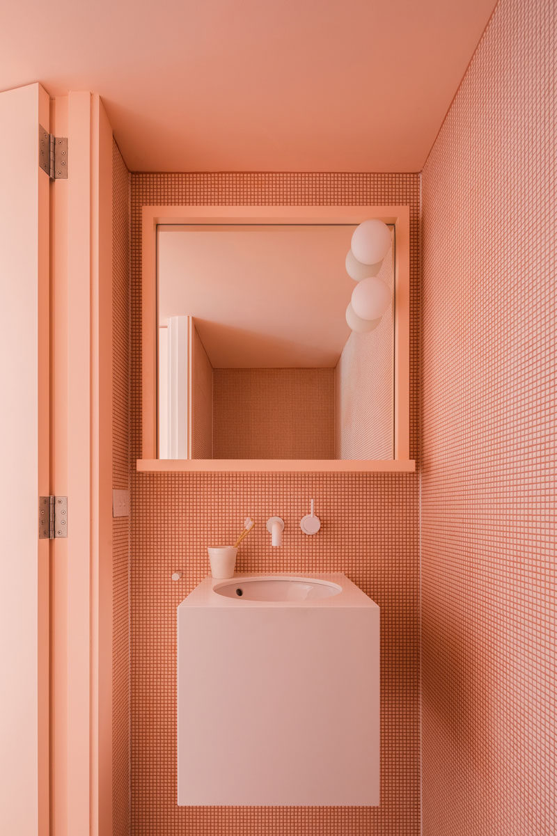 This modern half bath is covered in tiny peach tiles that match the peach ceiling, and creates a monochrome look