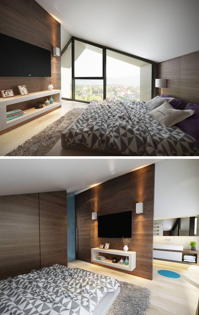 The windows in this modern bedroom follow the line of the roof, and dark wood accent walls have been used behind the bed and on the opposite wall to create a contrast to the white ceiling and light wood floors. Behind the wall with the tv is an ensuite bathroom.