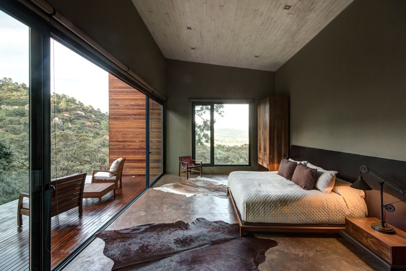 This master bedroom with a concrete ceiling, features a large sliding glass door that opens to provide access a private wood balcony.
