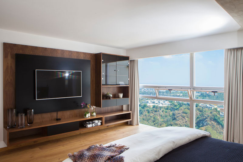 In this master bedroom, a custom wood entertainment unit with glass-enclosed shelves is the perfect place for displaying decorative items, while the large floor-to-ceiling windows are broken up by smaller windows that can be opened.
