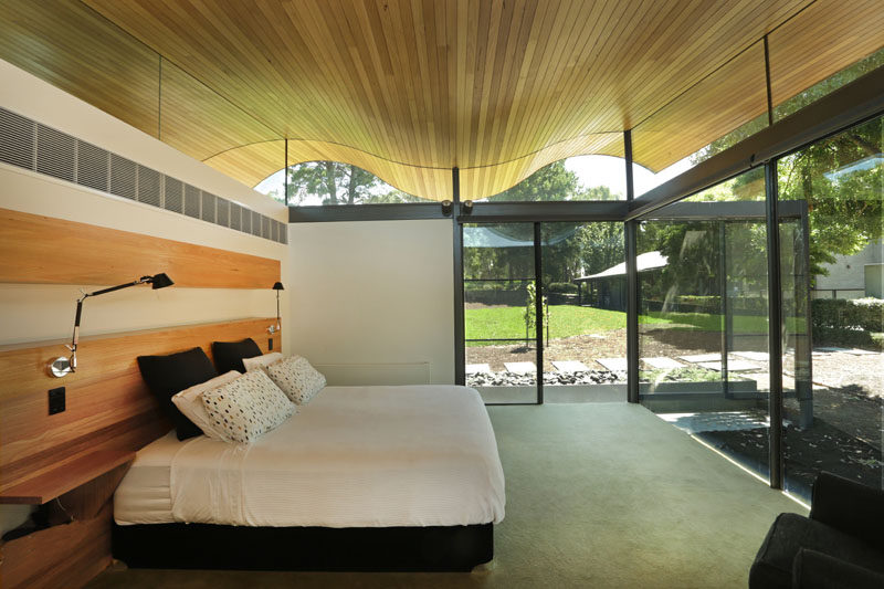 In this modern bedroom there's a softly rolling ceiling and large floor-to-ceiling windows and sliding glass doors that leads out into the backyard. The wood headboard behind the beds provides built-in side tables, lights, and a shelf that can be used to display anything from photos to flowers to art.