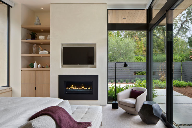 In this modern bedroom, there's a built-in fireplace with a recessed TV positioned above it, and large floor-to-ceiling windows keep the bedroom cozy and bright. Built-in shelving and storage also makes sure that the room stays organized and tidy while the built-in lights in the shelves highlight personal decorative items.