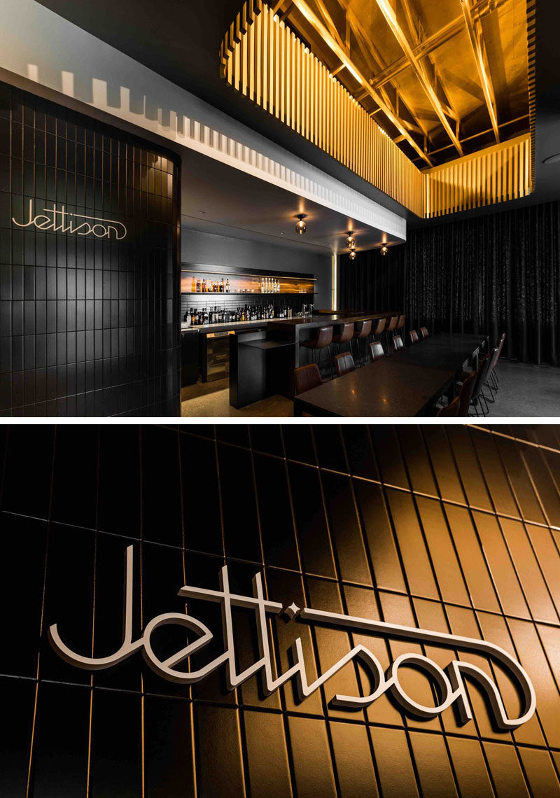 This modern and luxurious cocktail bar has a rich walnut bar with dark grey walls, brown leather seats, a black curtain on the back wall and painted gold touches to create a speakeasy atmosphere.