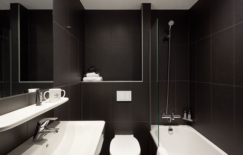 This modern black and white bathroom feature large black tiles and a white bath, vanity, toilet and shelf.
