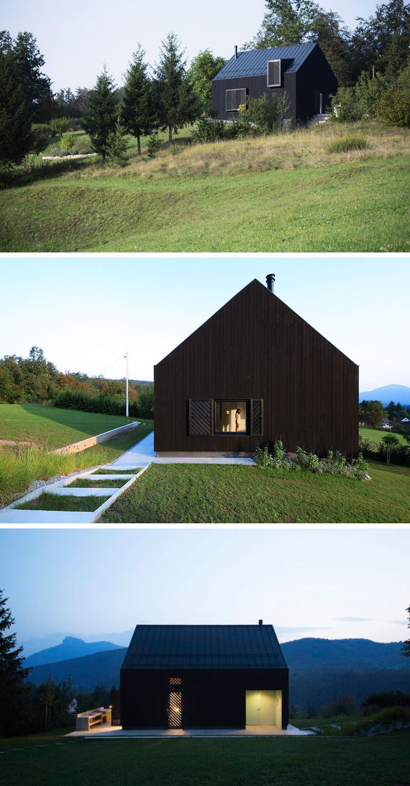 This small modern black house sits on a slope in the countryside of Croatia, and the white and lofty interior is a strong contrast to the exterior.