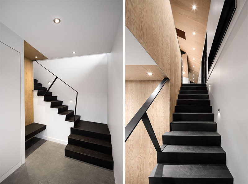 Light wood and white walls contrast these black stairs leading up from the basement to the main level of the home.